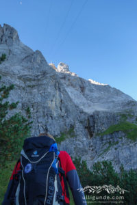 Während wir die ersten Höhenmeter machen, leuchtet der Gipfel der Zugspitze im Morgenlicht.